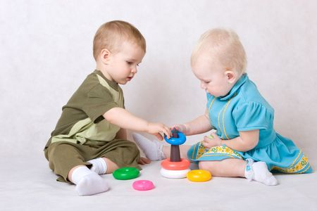 a boy and a girl of one and a half years old play pyramid sitting on the floor