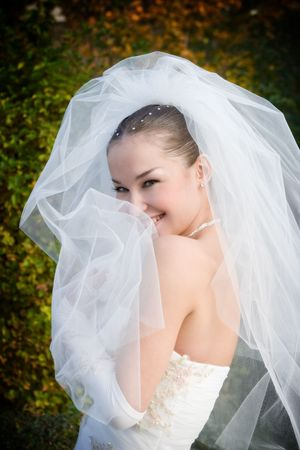 a smiling beautiful bride hides into her veil