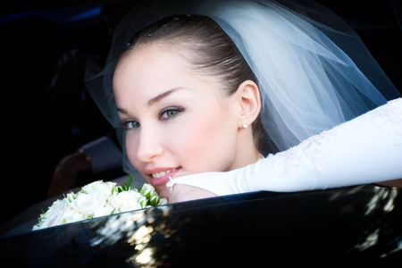 a bride smiles in the car photo