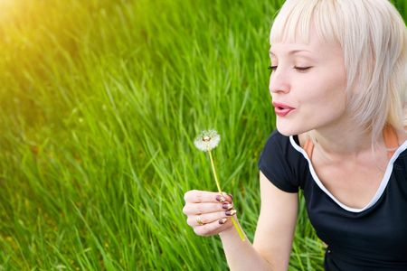 blond pretty girl blowing on the dandelion photo