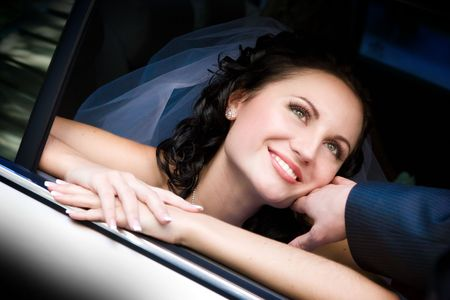 happy bride looks out of the car
