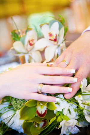 a hand of a groom and a hand of the bride with wedding rings on the flower bouquet Stock Photo - 3200033