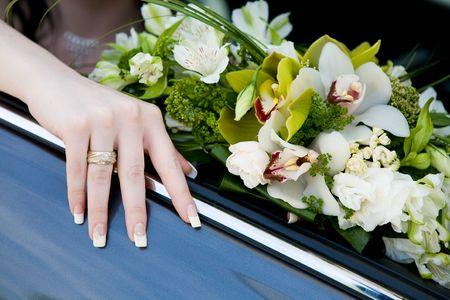 hand of the bride with wedding ring on the car and flower bouquet photo