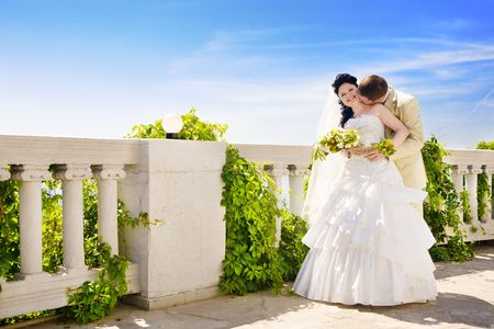 fense: kiss of the newly-married couple near the fense in summer Stock Photo