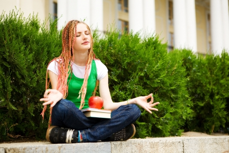 tresses: girl with a book meditating near the school