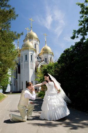 a newly married couple: groom kisses hand of bride near the chirch