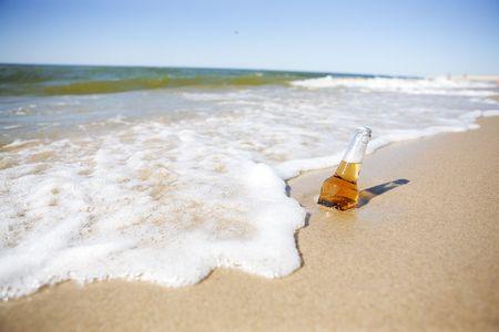 vasos de cerveza: Botella de cerveza en una playa Foto de archivo