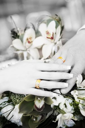 hand of groom and hand of bride with wedding rings on the flower bouquet in black and white photo
