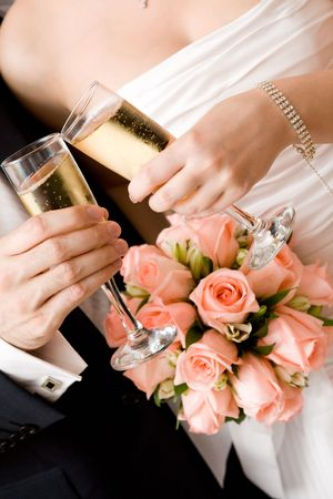 bride and groom with glasses of champagne and red rose bouquet Stock Photo
