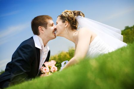 bride and groom kissing in the park Stock Photo