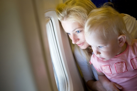 airport window: mother and child look through the window of the airplane