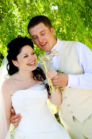 bride and groom blowing on the dandelions photo