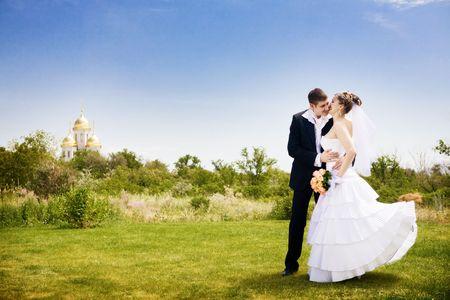 groom kisses bride near the church Standard-Bild