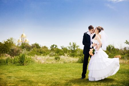 groom kisses bride near the church photo