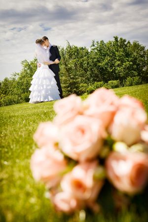 groom kisses bride and a flower bouquet near by