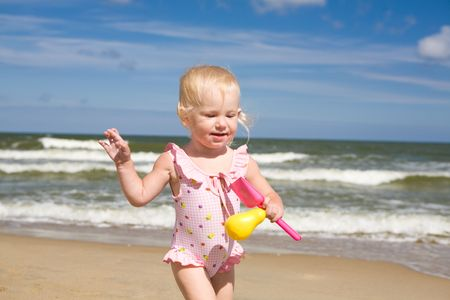 small girl with toys on the seashore photo