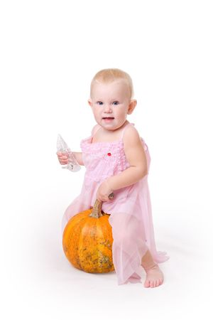 smiling little girl embraces pumpkin and a crystal shoe near by photo
