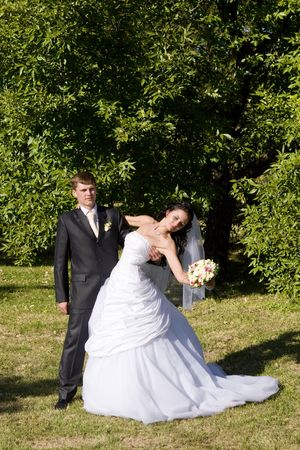bride and groom dance in the park photo