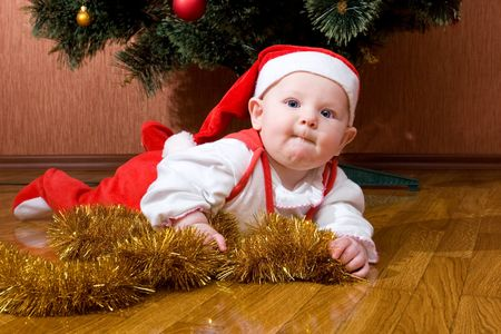 Babie: Little baby as Santa in red cap laying on the floor with gifts