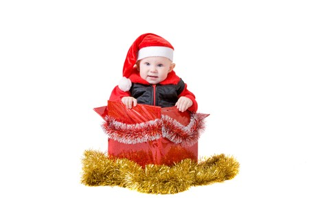 happy infant with red cap in a decorated christmas box photo
