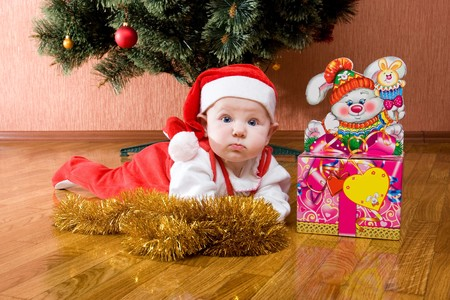 Little baby as Santa in red cap laying on the floor with gifts photo