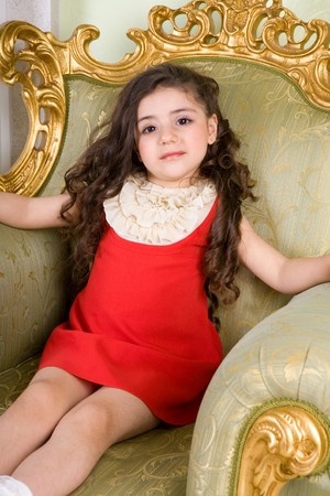 small girl with long hair in the armchair photo