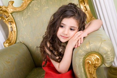 small girl with long hair in the armchair Stock Photo