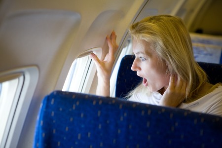 woman flying: surprised girl in the airplane Stock Photo