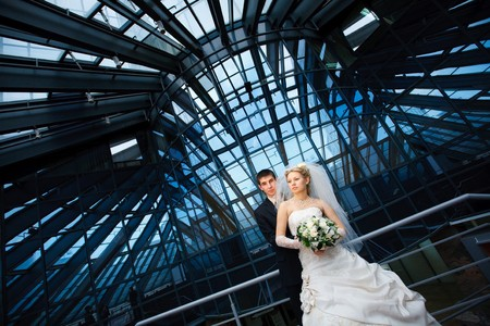 bride and groom under the glass ceiling