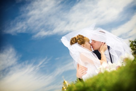 newly married couple: bride and groom kissing in the park Stock Photo