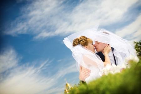 bruid en bruidegom kussen in het park