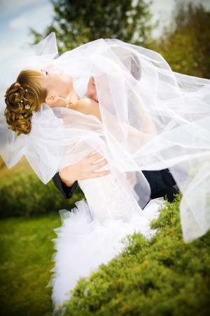 bride and groom kissing in the park photo