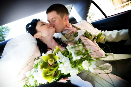 bride and groom kiss in the car