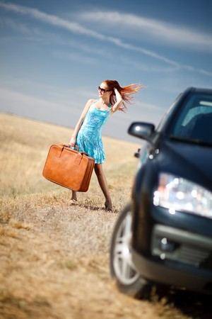 laughing girl with the suitcase near the car Standard-Bild
