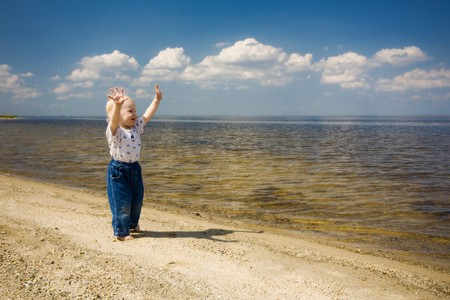 barefoot child is happy on the river bank photo