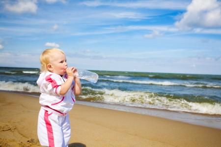 child drinking water at the seashore photo