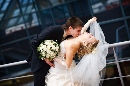 groom and bride kiss under the glass ceiling