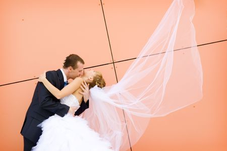 kiss of bride and groom near the wall photo
