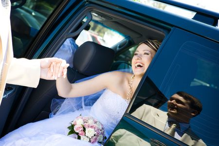 helps: groom helps to bride to leave a car Stock Photo