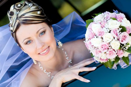 happy bride with flower bouquet siting in the car photo