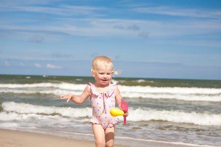 child run on the beach photo