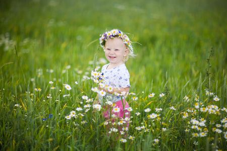 child with flowers in the field photo