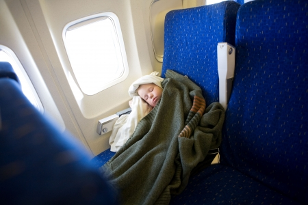 small girl sleeping in a plane photo