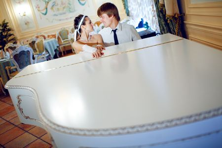 happy bride and groom at the piano Stock Photo - 5485692