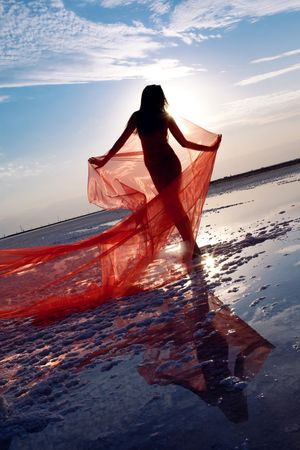 nude outdoors: silhouette of the naked girl in red shawl