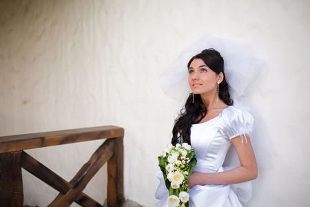 bride by the white wall looking up Stock Photo - 5687204