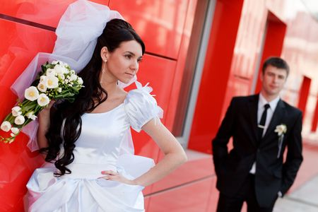 bride and groom by the red wall Stock Photo