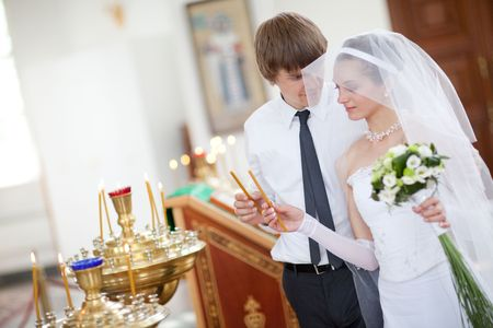 couple lighting candles in a church photo