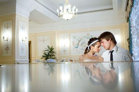 glückliche Braut und Bräutigam am Klavier