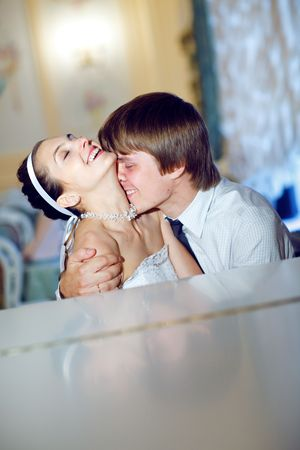 happy bride and groom kiss at the piano Stock Photo - 5687188